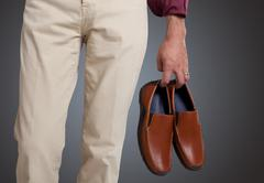 Stock Photo of Man holding the shoes in hand close up