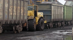 Tractor dragging train cars in coal port Stock Footage
