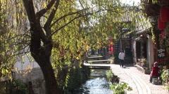 Man walking beside Lijiang canal, China Stock Footage
