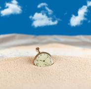 Vintage pocket watch semi buried in the sand Kuvituskuvat