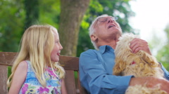 4K Grandfather & granddaughter chatting as they sit in garden with pet dog - stock footage