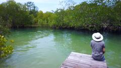Asian girl wearing hat sits on a small pier next to the Intertidal forest Stock Footage