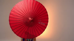Japanese Geisha performer posing with sun parasol in studio, slow motion Stock Footage