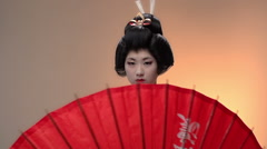Japanese geisha performer posing in Studio with umbrellas, slow motion Stock Footage