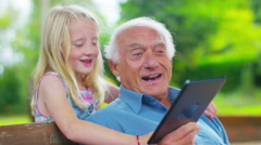 4K Grandfather & granddaughter sitting in the garden, looking at tablet computer Stock Footage