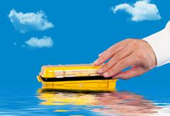 Opening a water resistant case floating in the water - stock photo