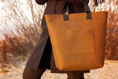 closeup of brown felt bag in woman hand - stock photo