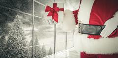 Composite image of mid section of santa holding gift - stock photo