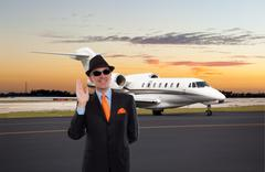 Business man waving near a private jet Stock Photos