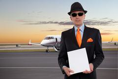 Business man next to a private jet holding a stack of papers - stock photo