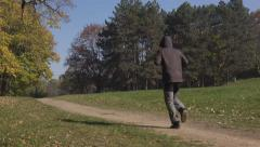 Man jogging in the park in early autumn morning Stock Footage