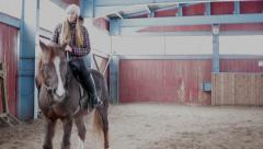Young woman ride a horse  at the stable Stock Footage