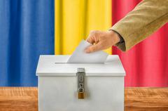 Man putting a ballot into a voting box - Romania - stock photo