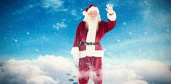 Stock Photo of Composite image of jolly santa waving at camera