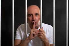 Man in jail gesturing to keep silence - stock photo