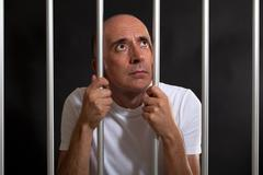Desperate and sad man behind bars - stock photo