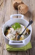Potatoes and mushrooms topped with sour cream in a casserole dish Stock Photos