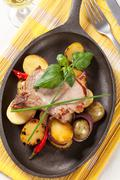 Roasted pork chop and potatoes on cast iron skillet - stock photo