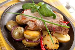 Roasted pork chop and potatoes on a skillet - stock photo