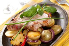 Roasted pork chop and potatoes on a skillet Stock Photos
