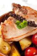 Juicy pork chop and potatoes in a terracotta bowl - stock photo