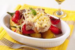 Pork chop with potatoes and red peppers topped with grated cheese - stock photo