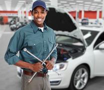 Smiling car mechanic in auto repair service. - stock photo