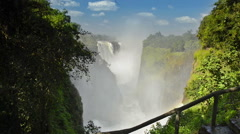 Victoria Falls Devils Cataract lockdown shot with mist and rainbow Stock Footage