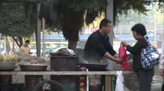 Chinese roasting chestnuts in street, China Stock Footage