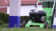 Gardener trimming lawn with electric mower Stock Footage