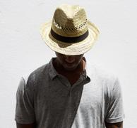 Male fashion model with hat looking down - stock photo
