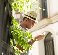 Happy young man with hat using mobile phone outside - stock photo