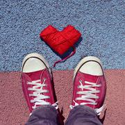man in sneakers and heart-shaped coil of yarn on the asphalt - stock photo