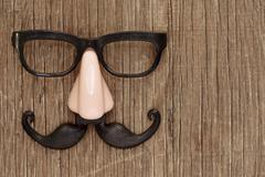 fake mustache, nose and eyeglasses on a wooden surface - stock photo