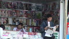 Reading the newspaper, newstand, China Stock Footage