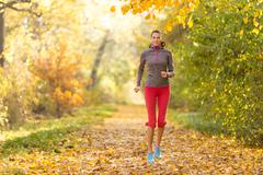 Female fitness model training outside and running - stock photo