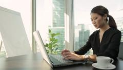 Young asian business woman working with her laptop in modern office. Dolly shot. Stock Footage