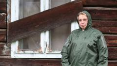 Woman in waterproof raincoat stands near uninhabited house Stock Footage