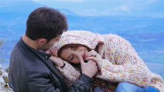 a man and a woman cuddle, hold hands and caress each other on top of a mountain - stock footage