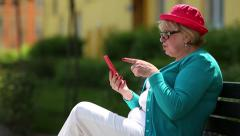 Woman in red cap sits on the bench and communicates via smartphone Stock Footage