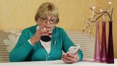 Senior woman with white smartphone drinks brandy Stock Footage