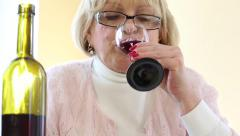 Depressed senior woman with bottle of wine. Woman drinking wine Stock Footage