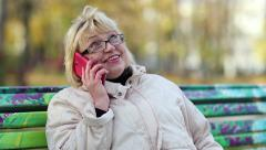 Woman sits on the bench and communicates via smartphone - stock footage