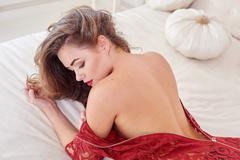 Fashion portrait of elegant young woman in red dress on bed in a luxurious in Stock Photos