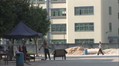 Chinese man sweeping dusty street Stock Footage
