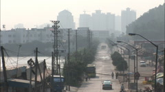 Dusty street by river, pollution, China Stock Footage