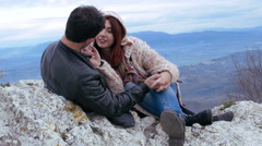 Young couple cuddling and kissing on the top of a mountain, excursion, love - stock footage