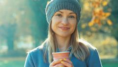 Young woman holding cup of tea smiling at camera in the park in the autumn ag Stock Footage