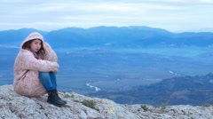 Young redhead in a natural context sat on rock, meditation, wind, cold Stock Footage