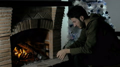 Meditative and pensive young man in front of a fireplace - stock footage
